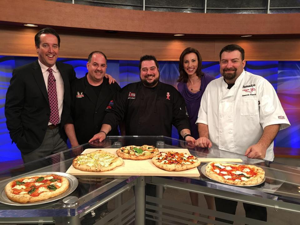 Jason and other chefs on a talk show displaying their pizzas.