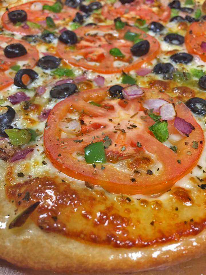 A pie with fresh tomato and chopped vegetables