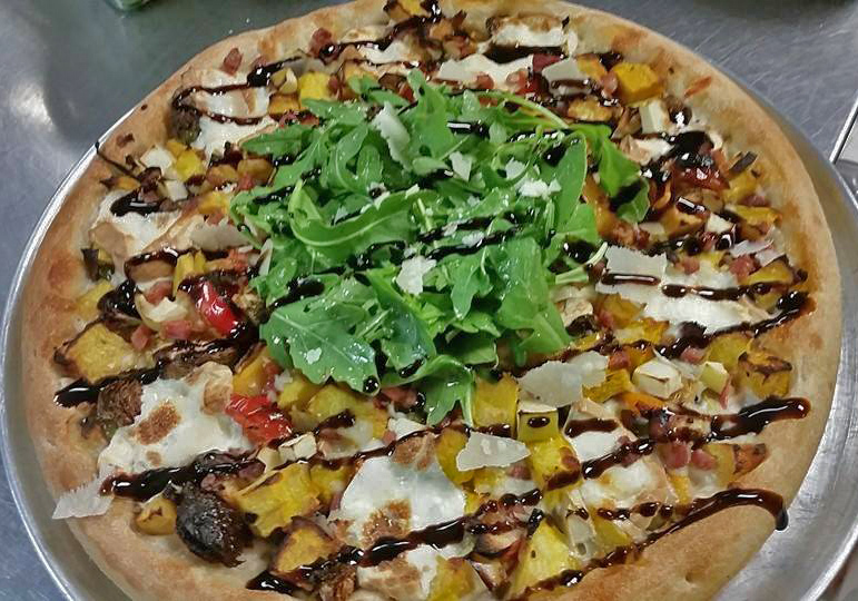 A Full pie with fresh arugula, chopped vegetables, and topped with a balsamic glaze