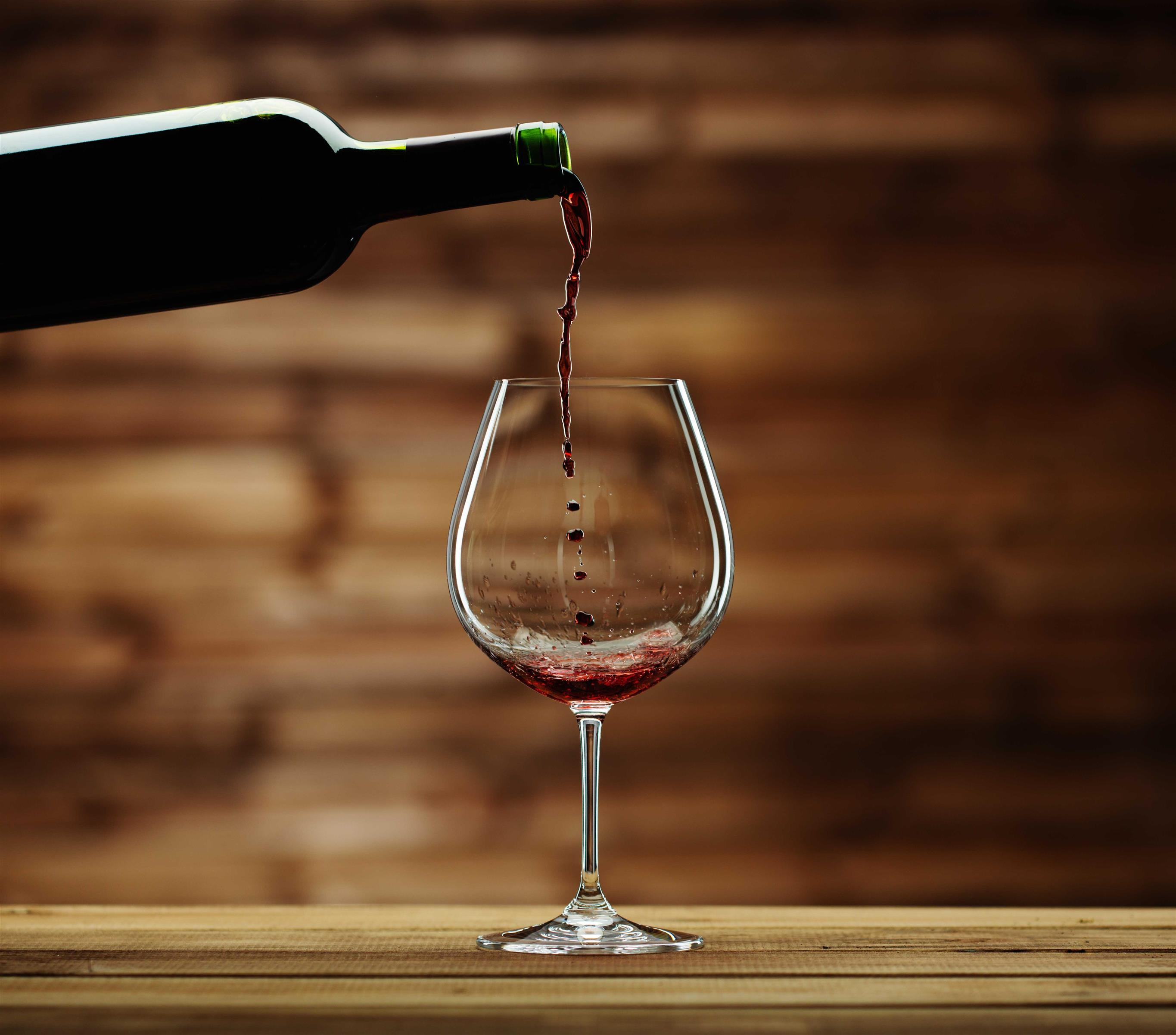 Red wine pouring out of a wine bottle into a glass with a blurred wood background