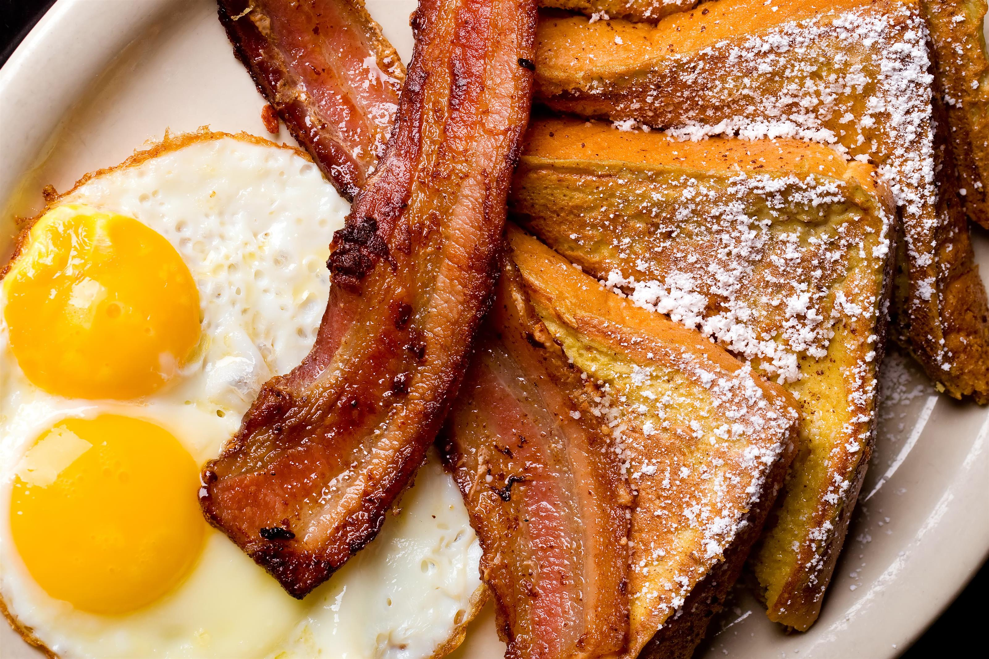 two sunny side eggs, bacon, and french toast