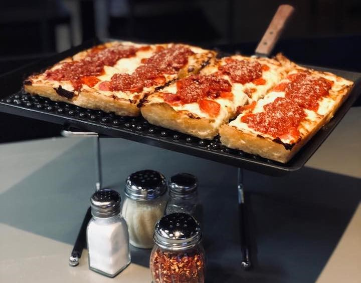 rectangular pepperoni pizza on a small, raised tray