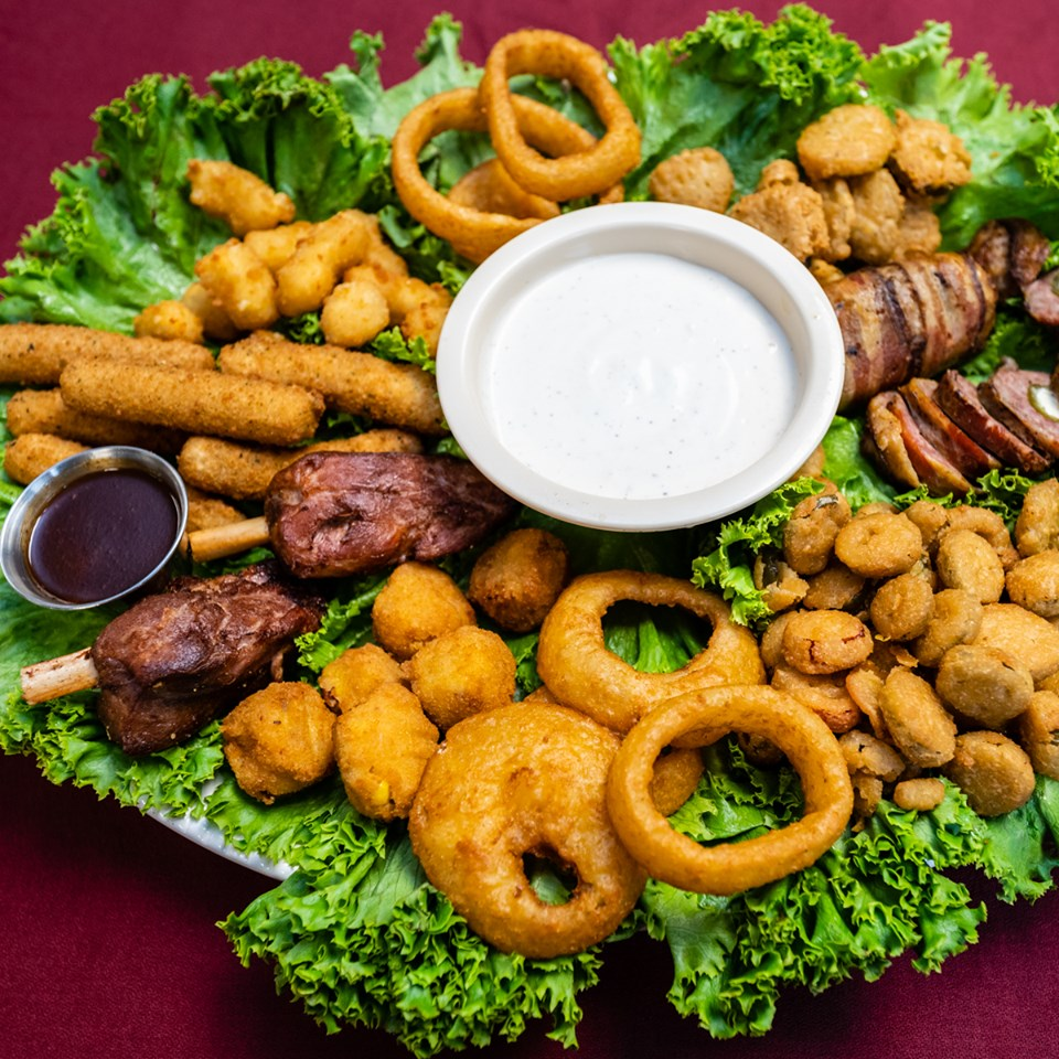 sampler platter on a bed of lettuce as garnish with rib tidbits, mozzarella sticks, onion rings, fried pickles, sliced sausage and hush puppies