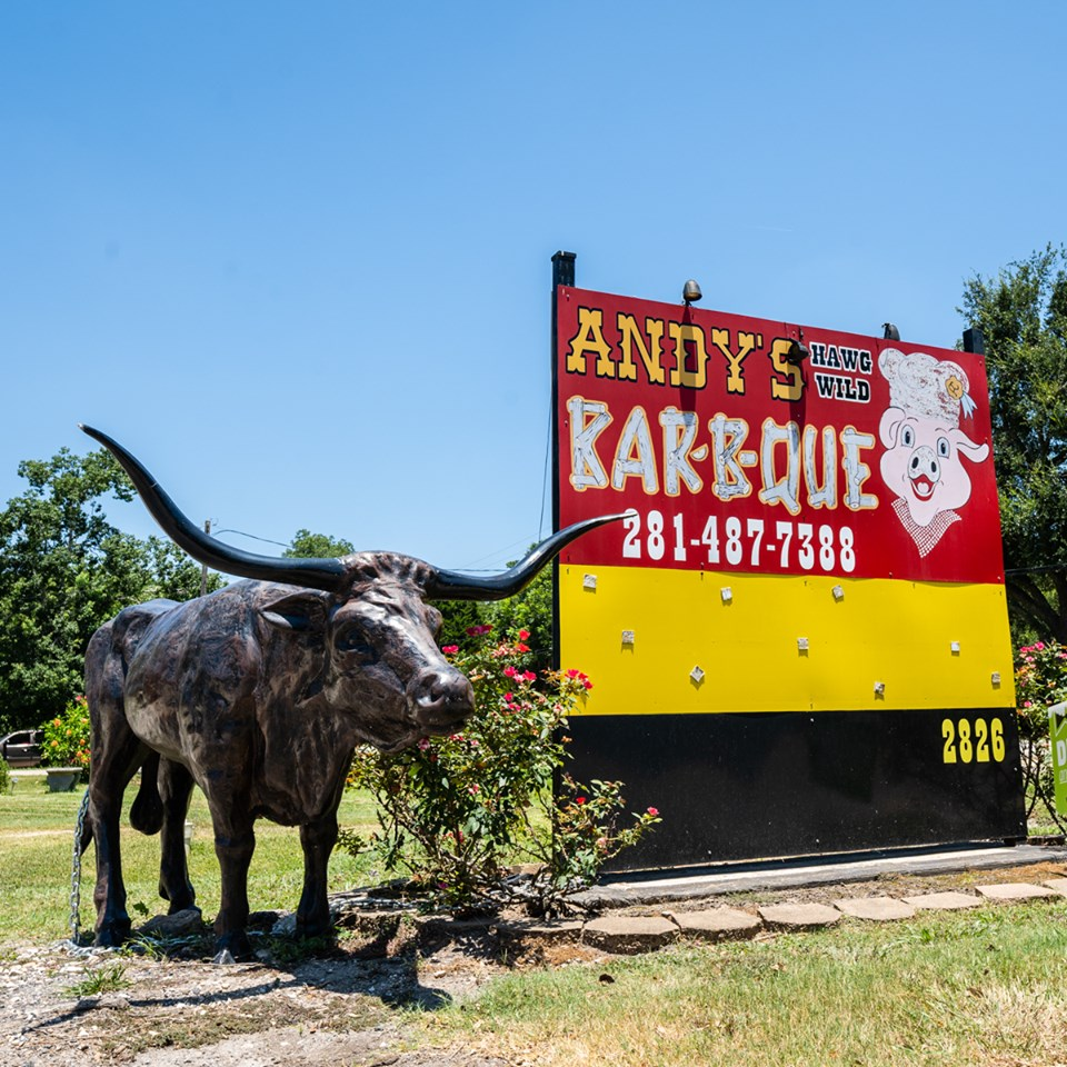 Andy's Hawg Wild Bar-B-Que sign outside next to a sculpture of a bull