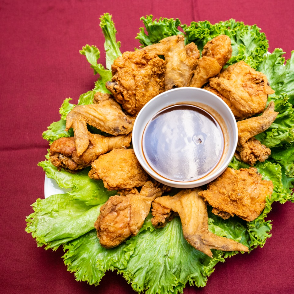fried chicken wings on a bed of lettuce as a garnish served with barbecue sauce