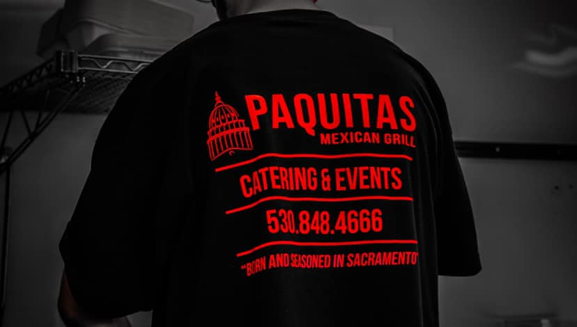 Worker with shirt saying Paquitas Mexican Grill Catering & Events 530-848-4666
