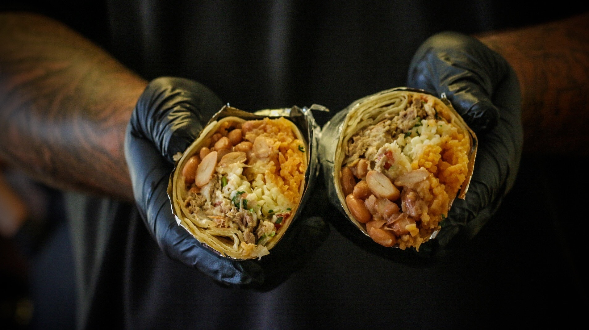Person holding burrito cut in half wrapped in tin foil