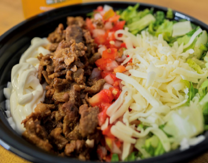 burrito ingredients in a bowl. Rice, beans, tomatoes, lettuce and cheese