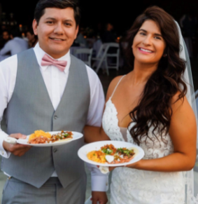 Bride and groom holding plates of food and smiling