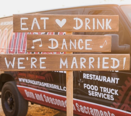 "Sign that says ""Eat, drink, dance, we're married"""