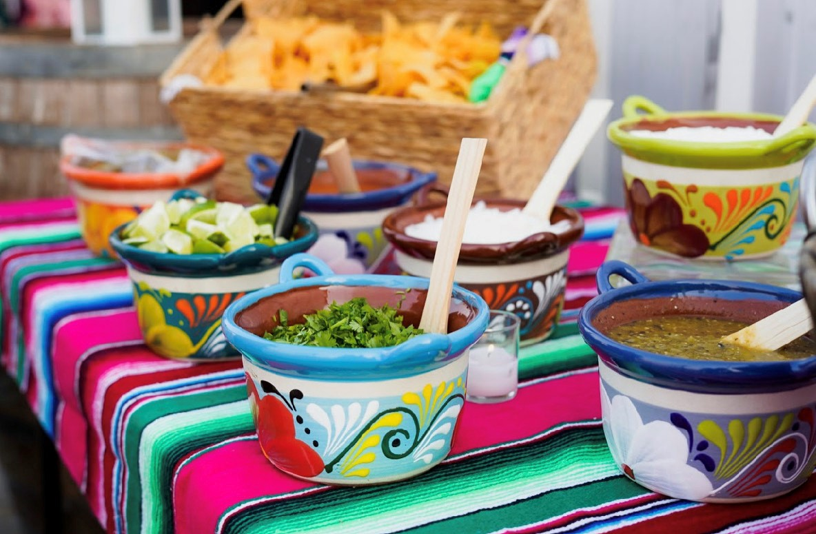 Bowls of salsa and taco toppings on a table with a basket of chips