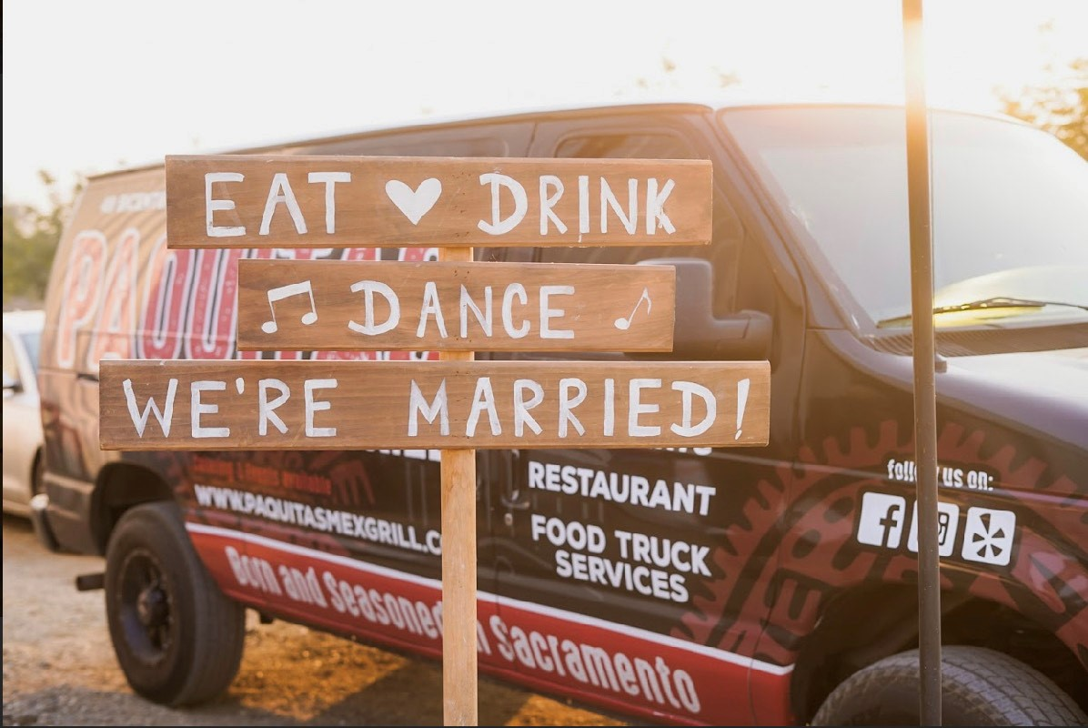 "A wooden sign that says ""Eat, Drink, Dance, We're Married"" in front of a Paquita's Mexican Grill van"