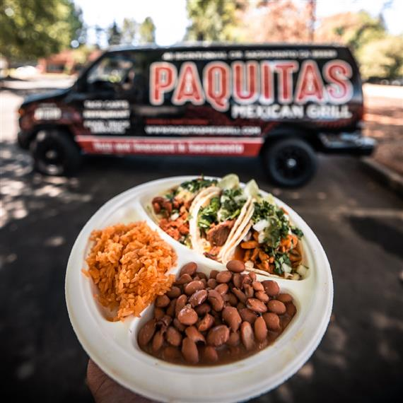Plate of beans, salad, meat in front of the catering truck