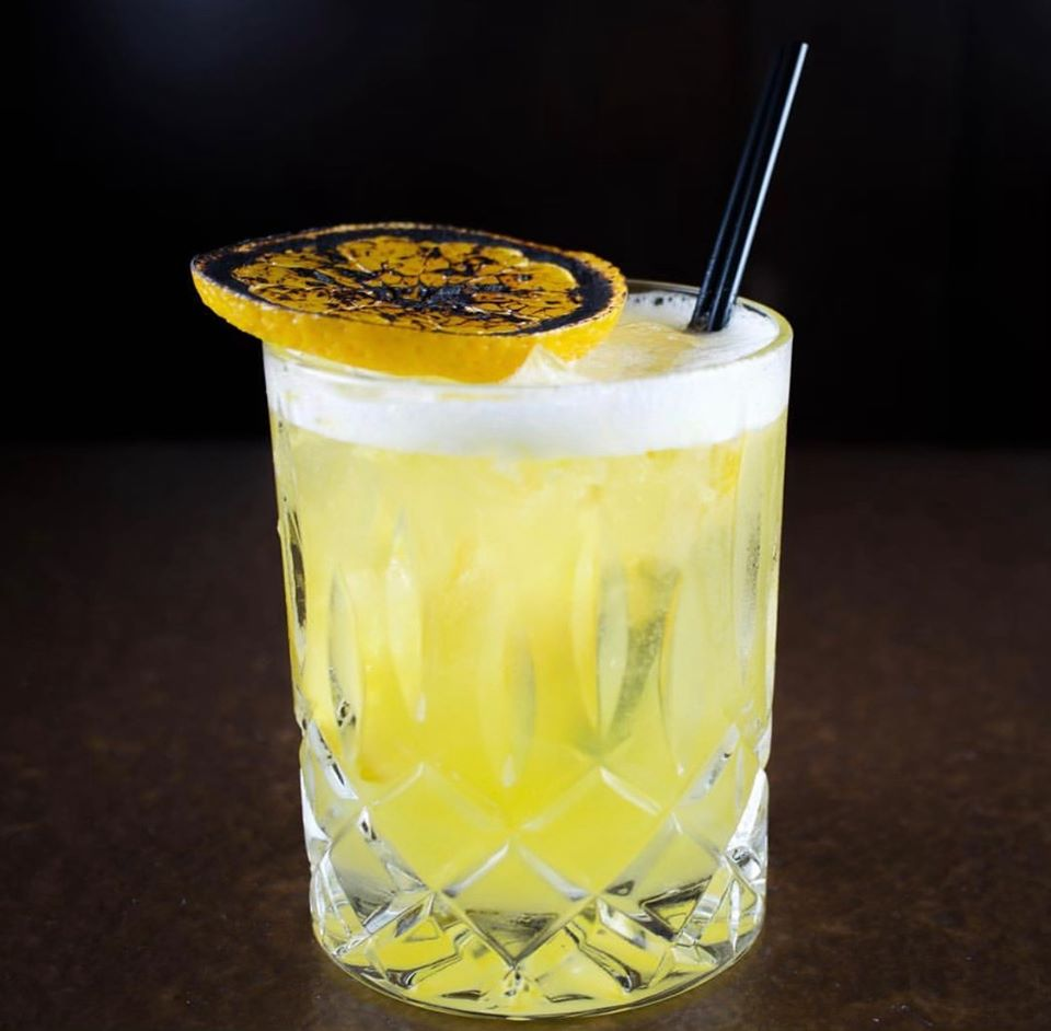 A cocktail garnished with a grilled lemon