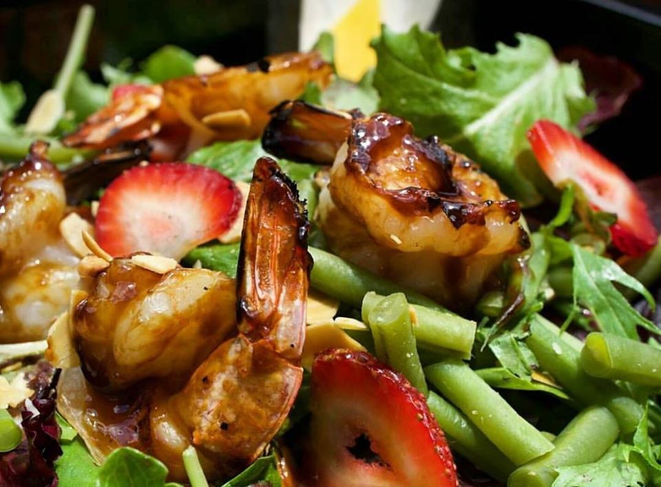 Shrimp over salad with strawberries and green beans