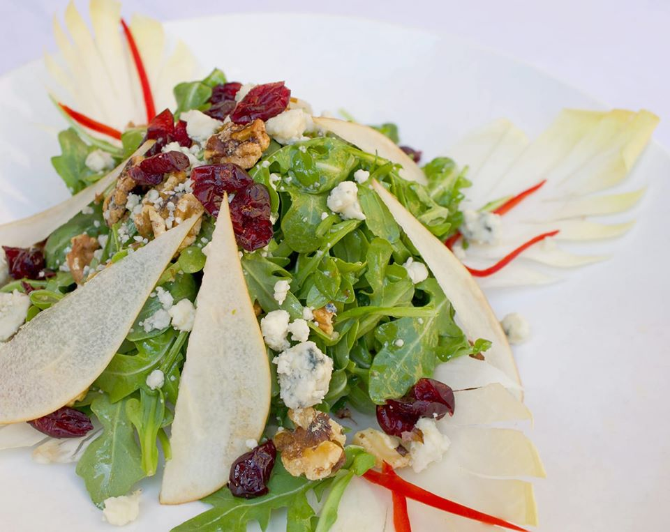 Arugula salad with pear slices, raisins, and walnuts