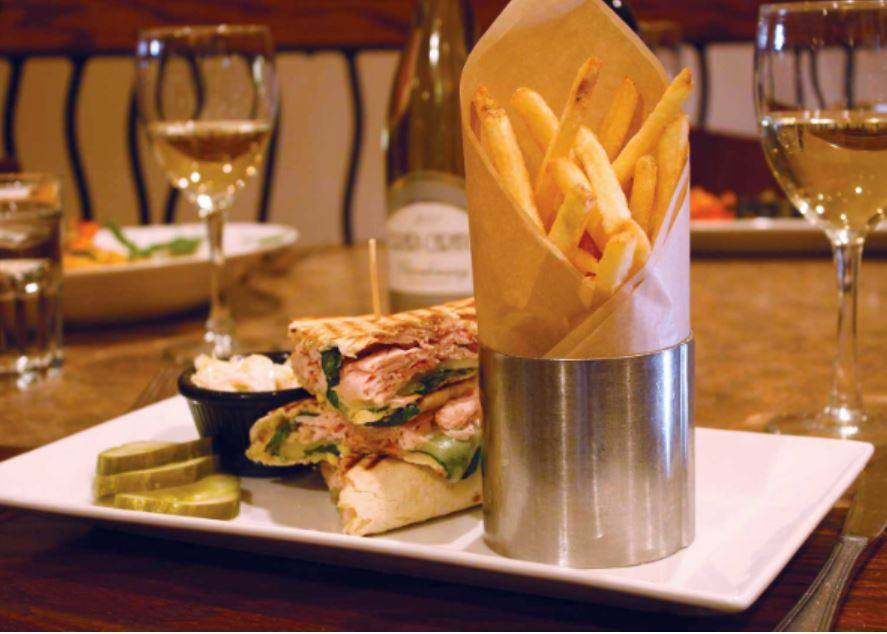Pressed sandwich on a plate with fries and two glasses of wine