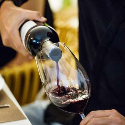 man pouring red wine into a glass