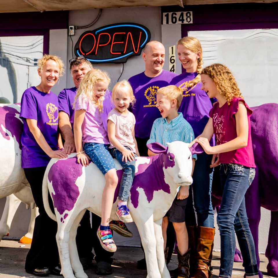 staff and family standing in front of the purple cow.