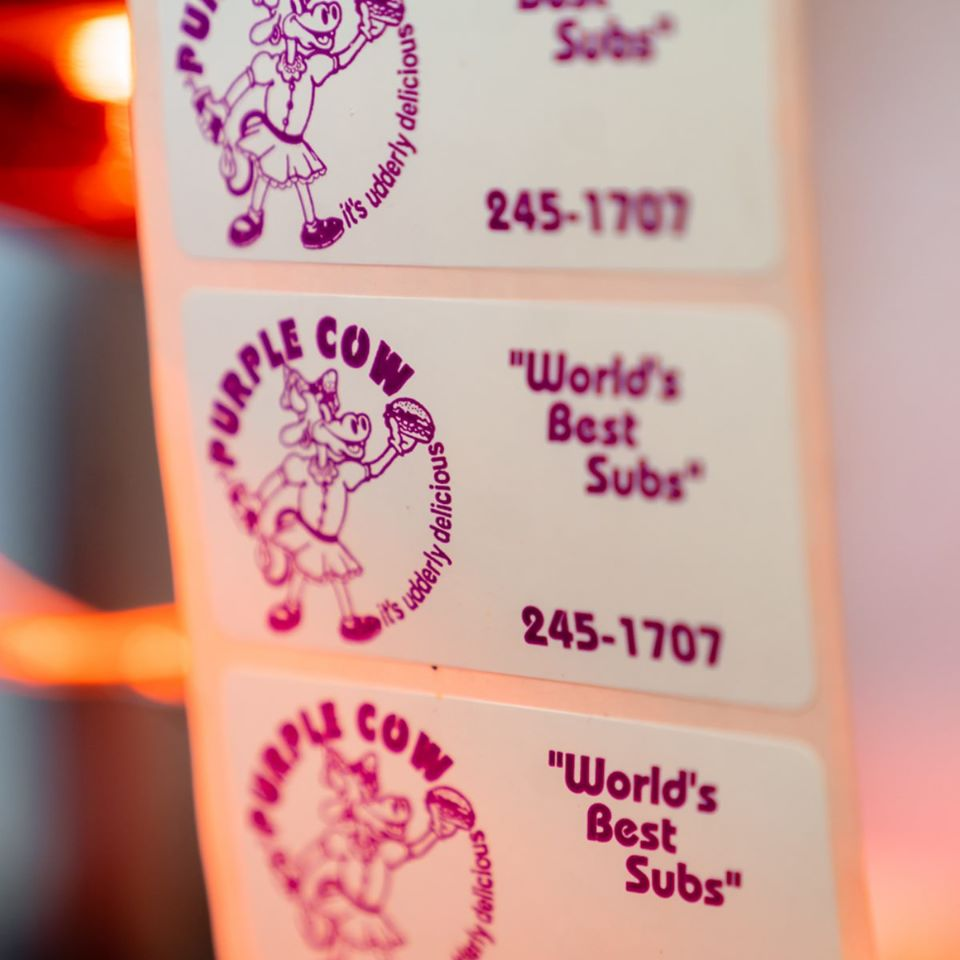 "roll of stickers that have the purple cow logo on it and say ""World's Best Subs"" 245-1707"