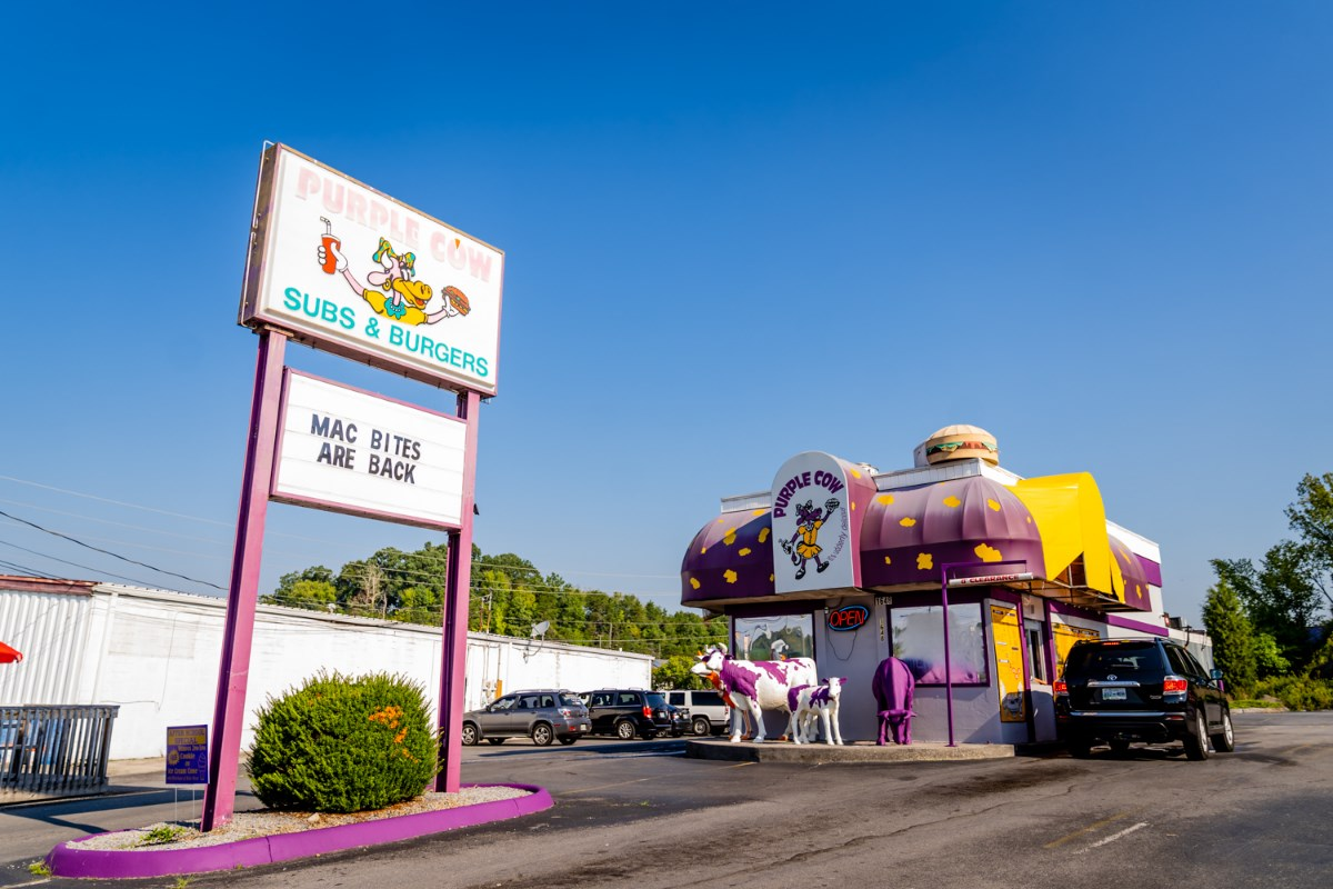 "Outside view of purple cow. Sign in front says ""Purple Cow Subs & Burgers"""