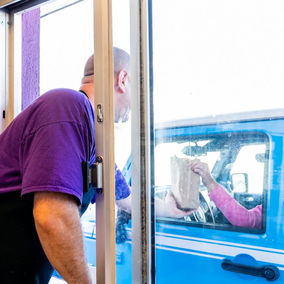 employee passing the order to a cuystomer at the drive-thru window.
