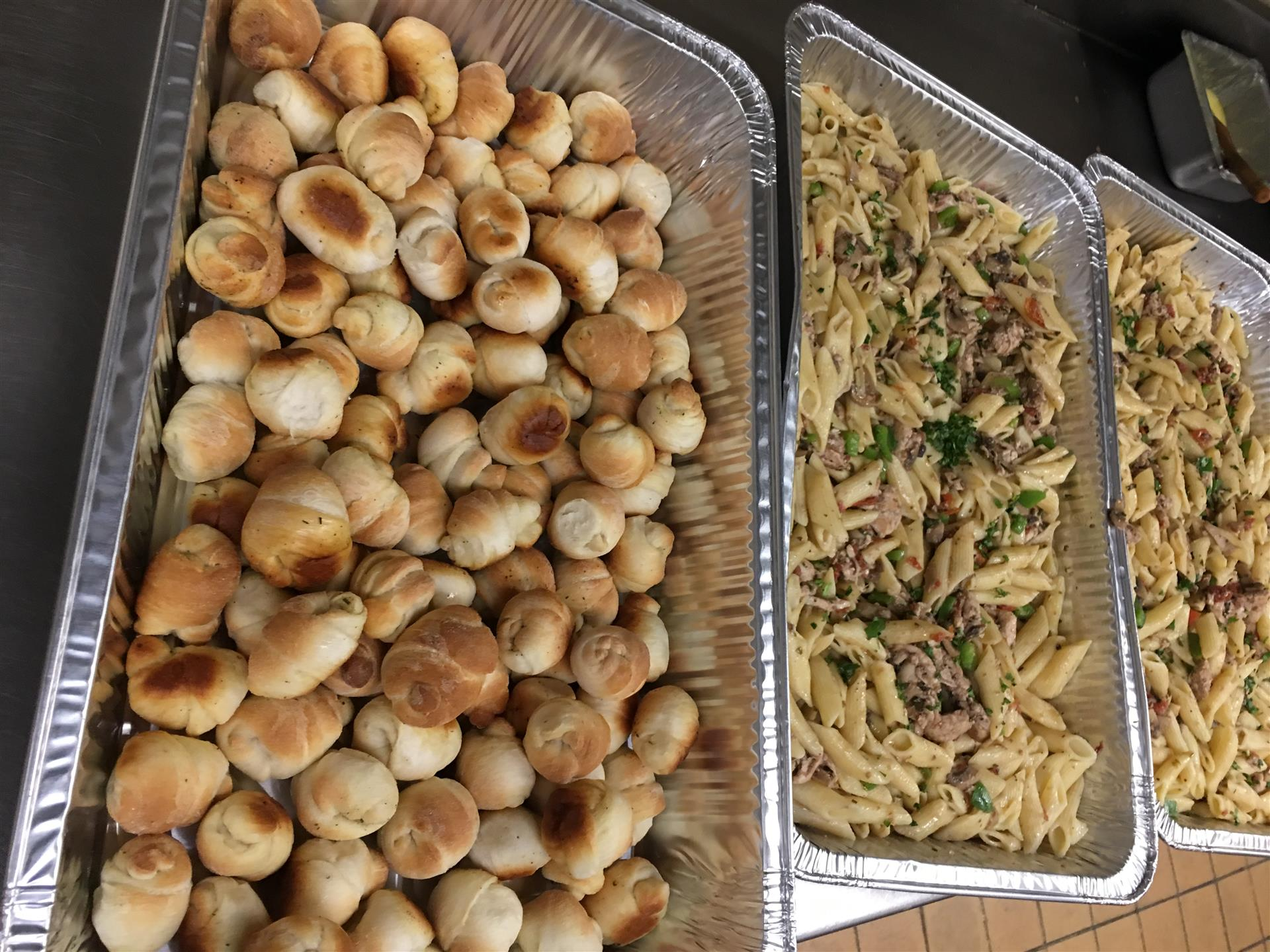 assortment of garlic knots and pasta in trays on a table