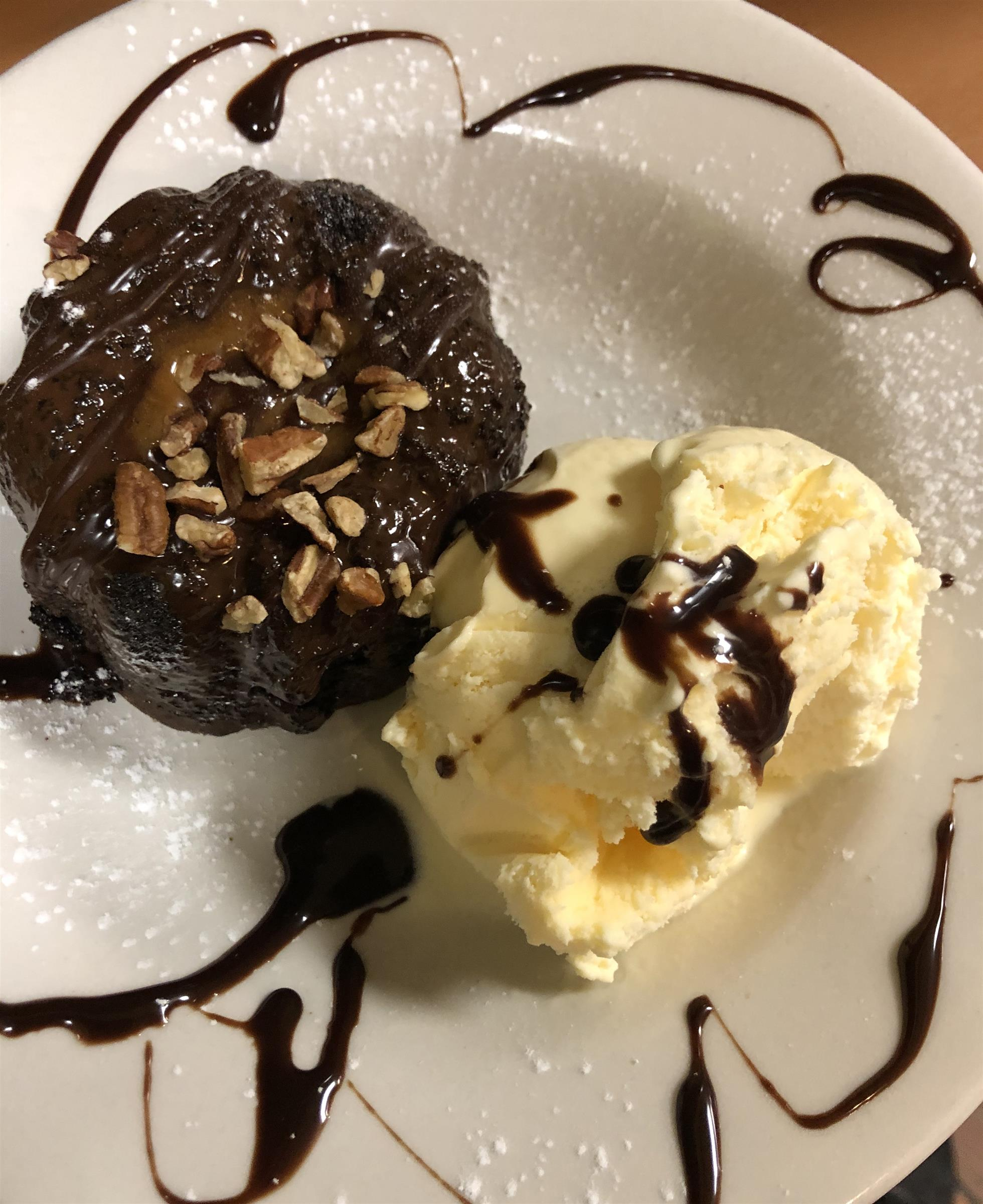 chocolate cake topped with nuts and a scoop of vanilla ice cream topped with chocolate syrup