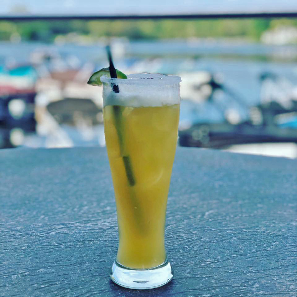 A cold drink resting on the deck in front of the water