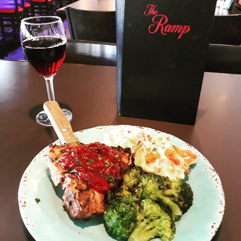 A chicken dish with tomato sauce drizzled on top, broccoli, and a glass of wine on the side