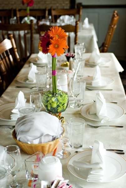 table set with glasses, utensils, and a flower with a side of bread