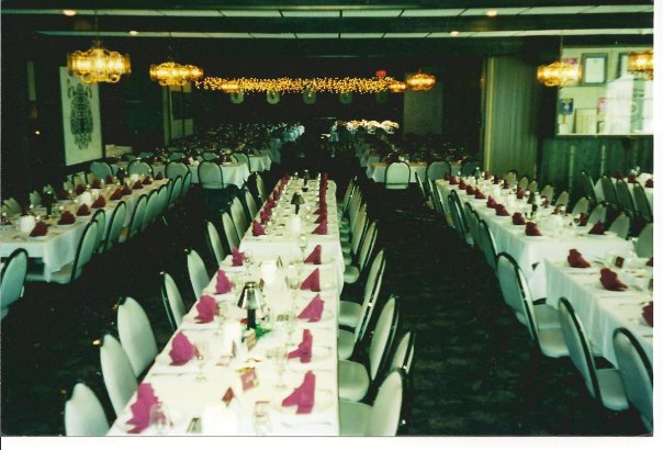 Room with long rectangular tables and chairs - the tables have plates, utensils and coffee mugs set up with roses as centerpieces