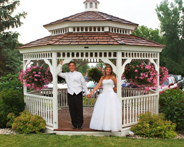 bridge and groom posing for a picture in gazebo