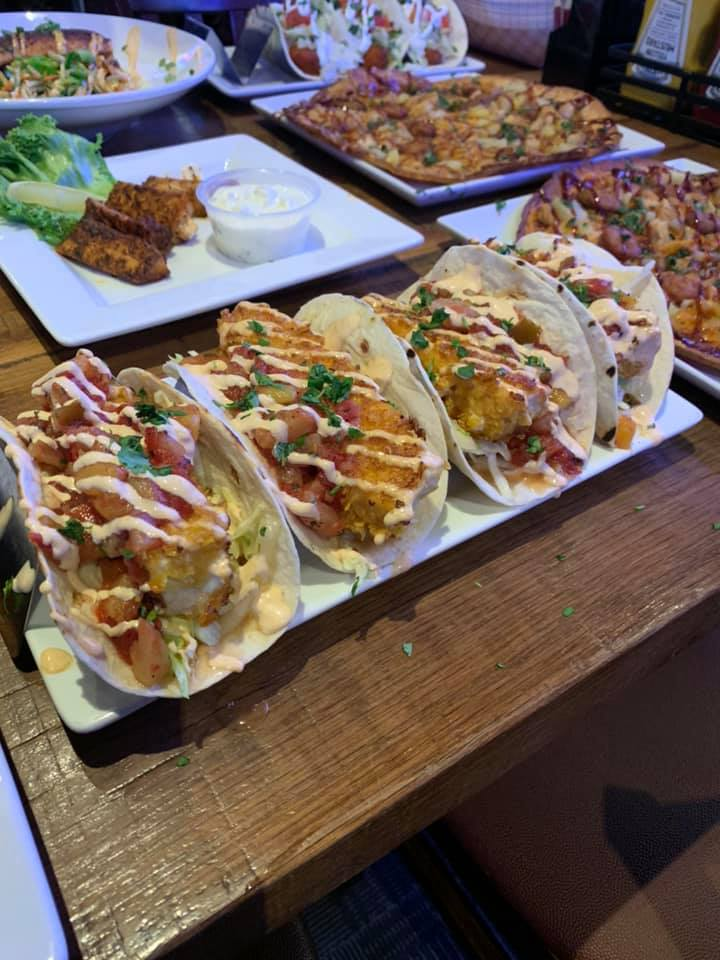 Table covered in plates of tacos, pizza, and wings