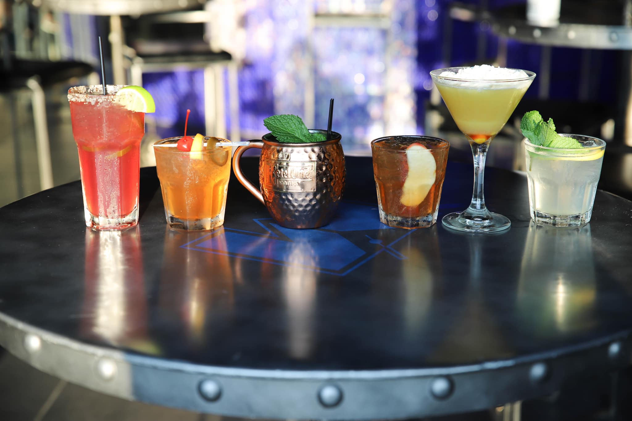 Assortment of cocktails lined up along bar