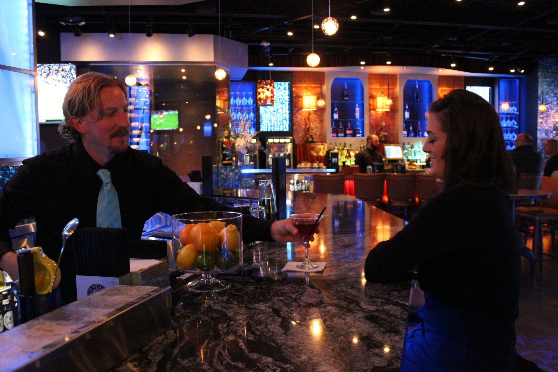 Bartender serving drink to person