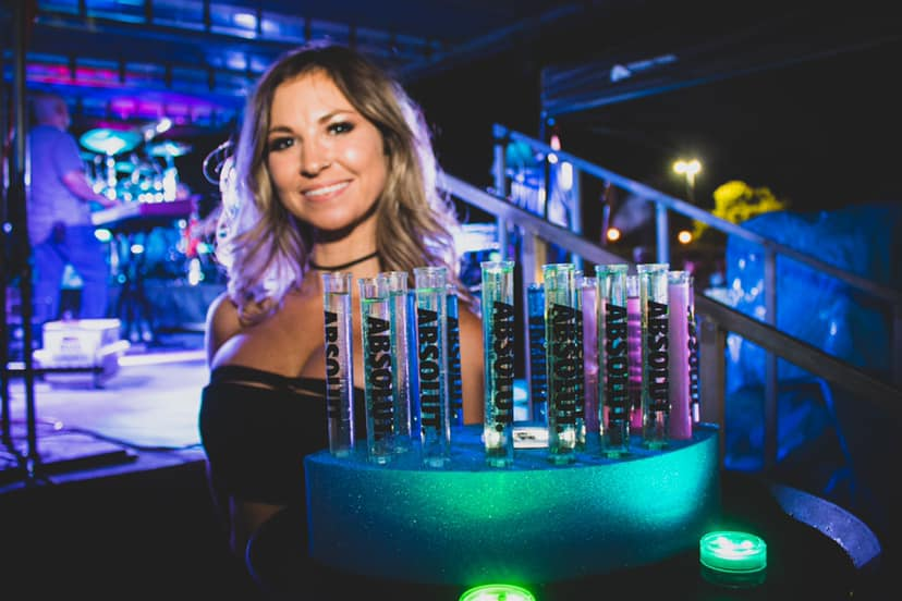 Woman holding alcholic shots of liquor in test tube