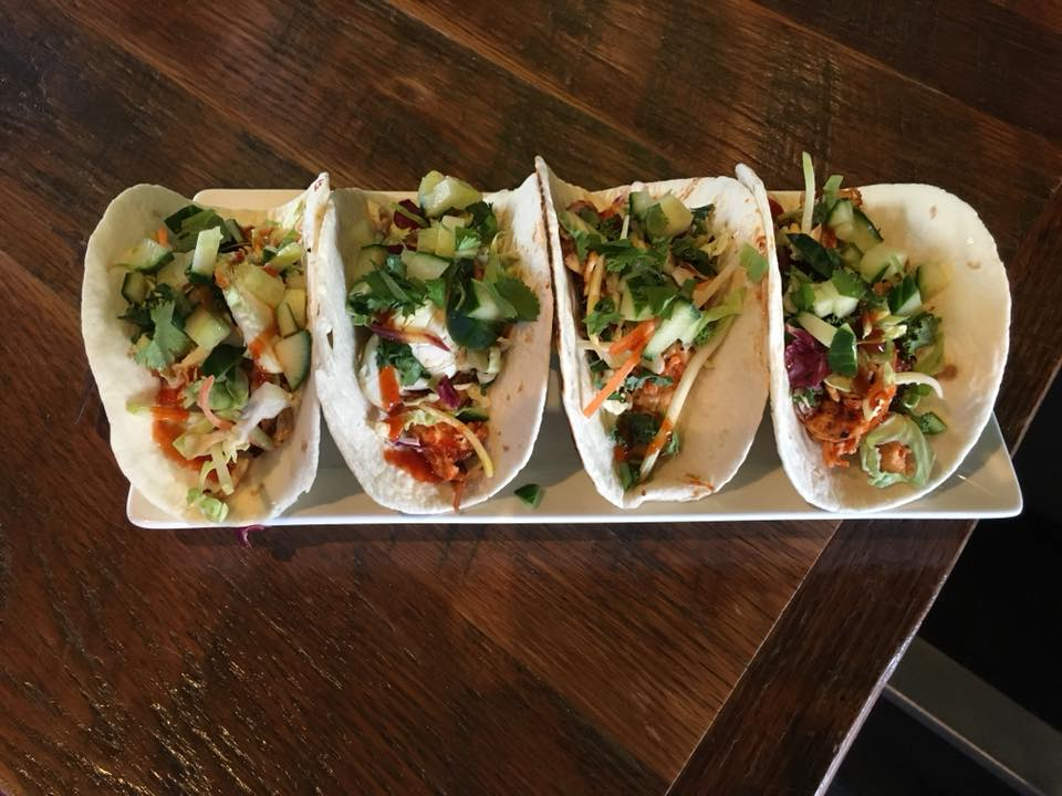 Four tacos lined up on plate