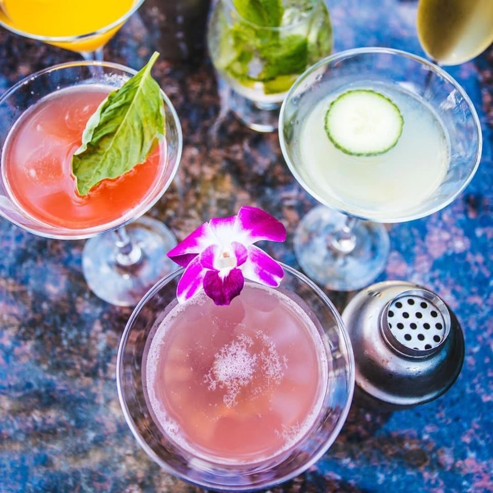 Assorted cocktails with floral garnishes