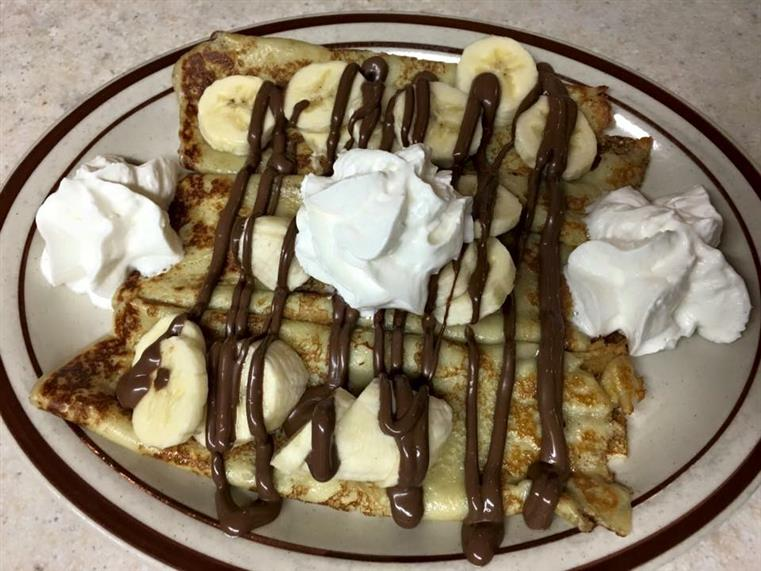 dessert crepes topped with banana slices, nutella dirzzle, and whipped cream