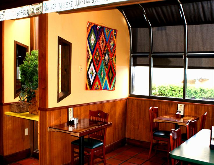 interior shot of the dining room with wood tables and chairs with an aztec style painting on the wall