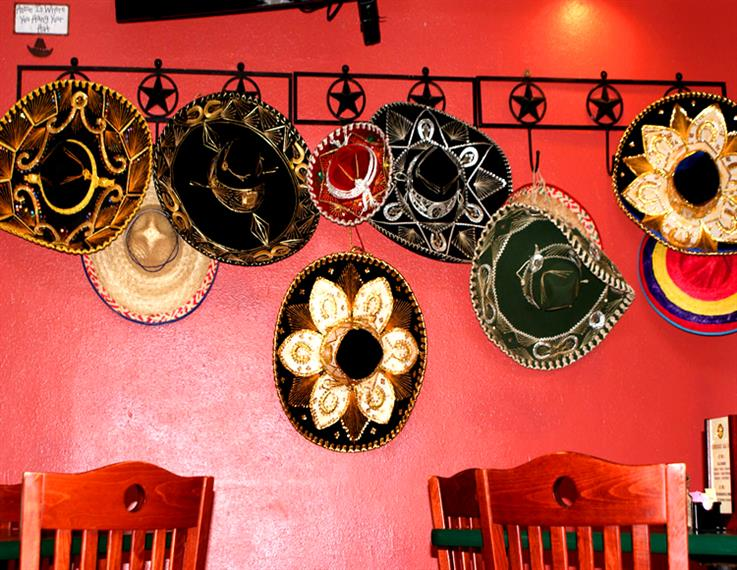 various sombreros hanging on the wall for decoration