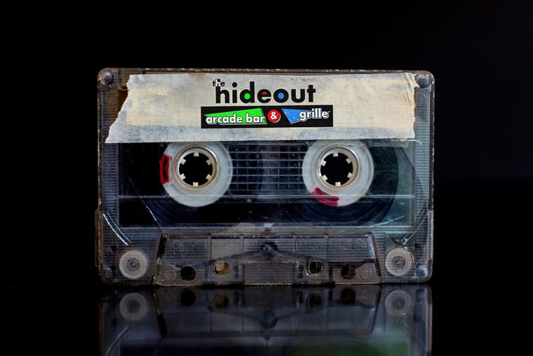 "A vintage cassette tape that says ""The Hideout Arcade Bar & Grill"""