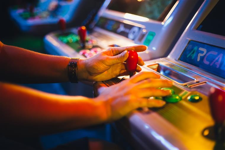 Two hands playing an arcade game