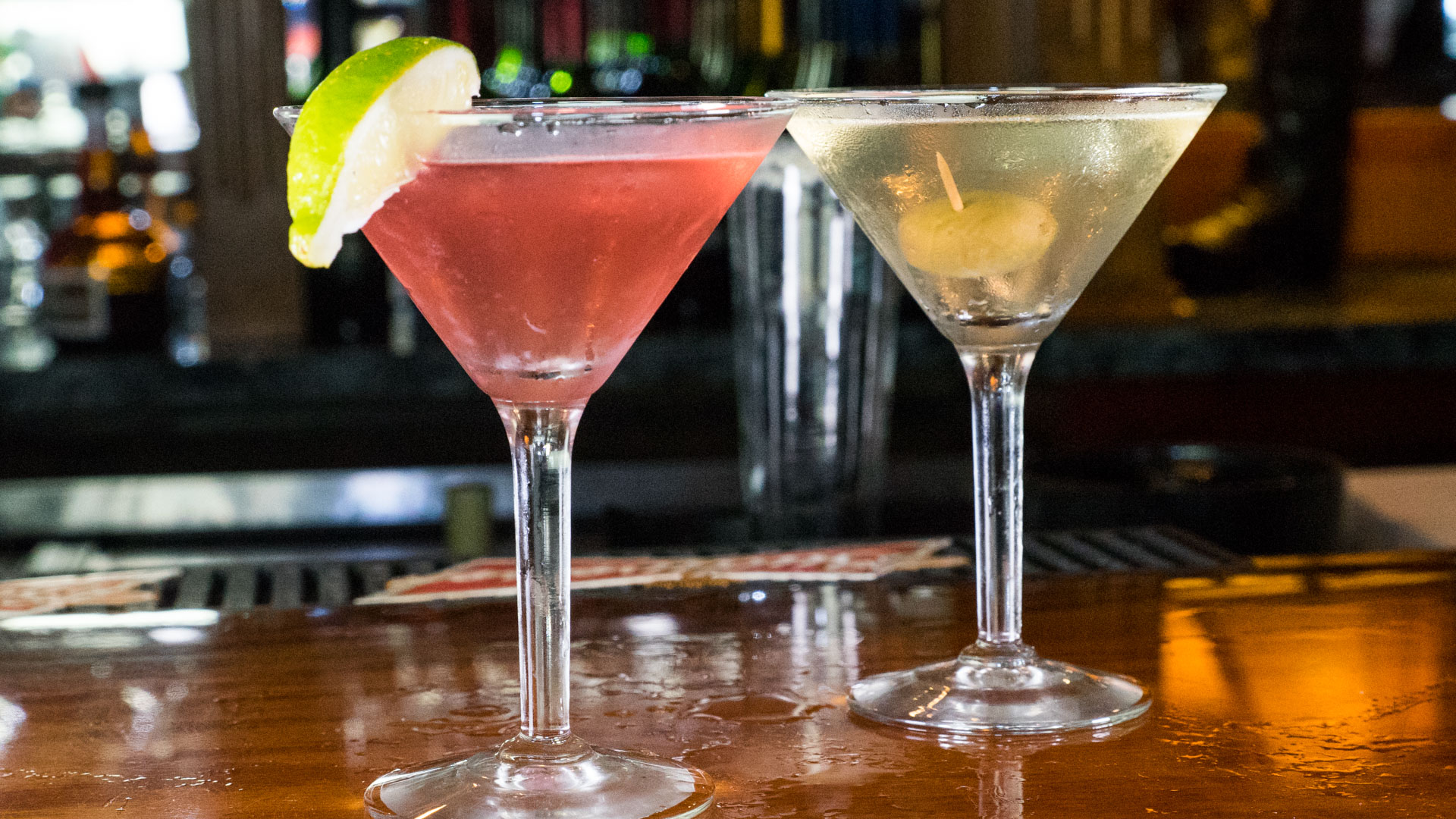 a cosmopolitan with a lime and a dirty martini with olives on the bar