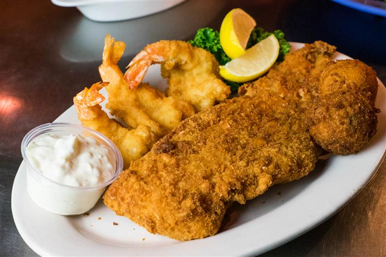 fried fish on a plate with fried shrimp, tartar sauce and lemon wedges.
