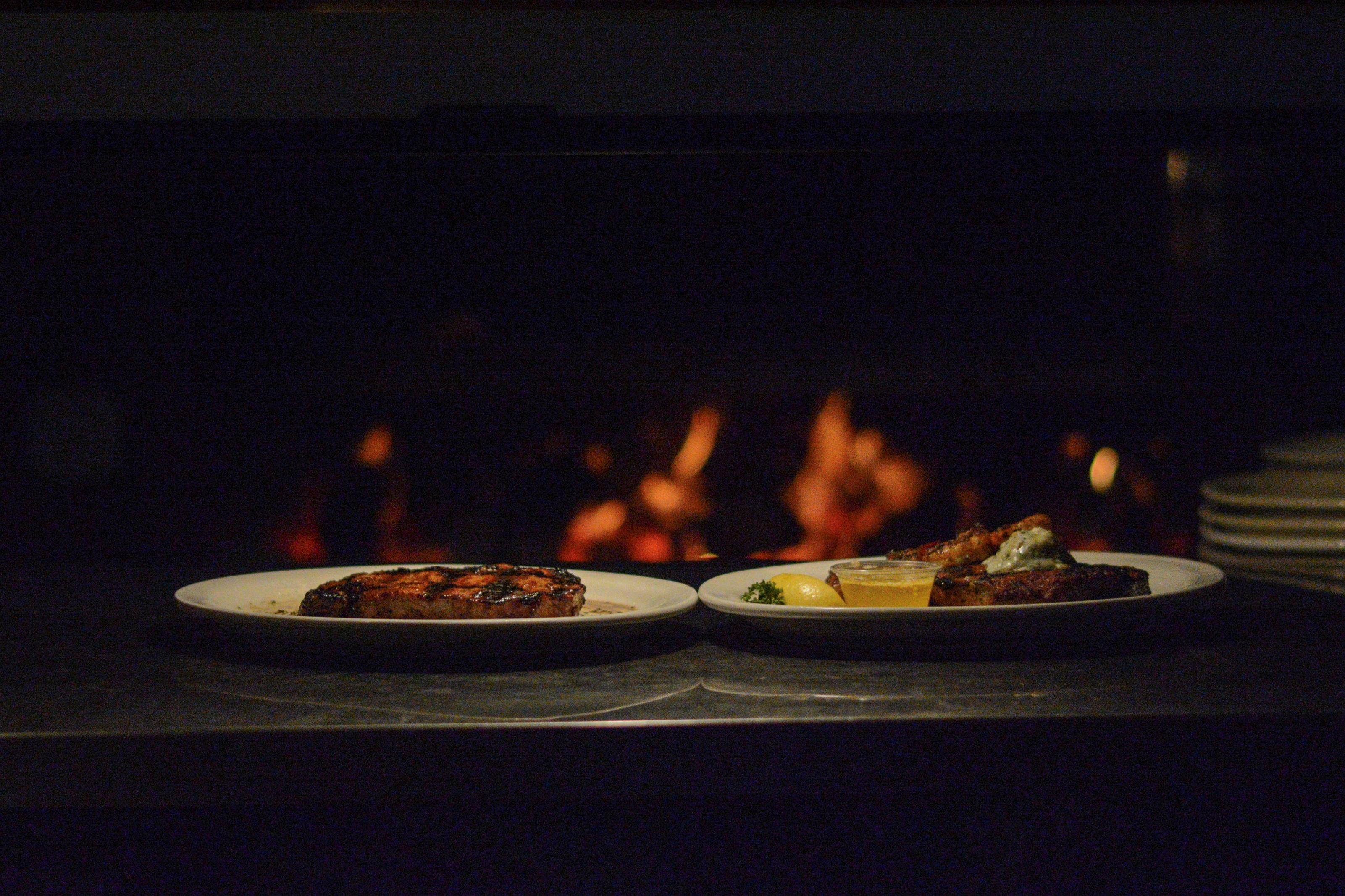 two plates of grilled steaks sitting in front of the open flame grill. the steak on the right is topped with grilled shrimp