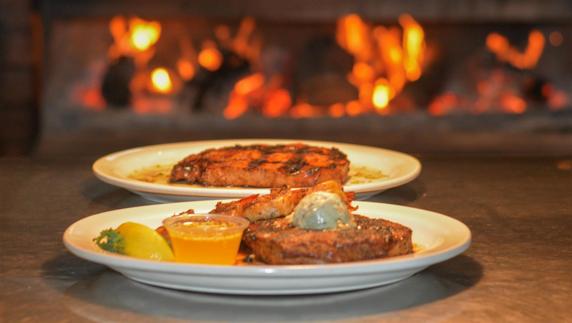 two plates of grilled steaks sitting in front of the open flame grill. the steak in front is topped with grilled shrimp