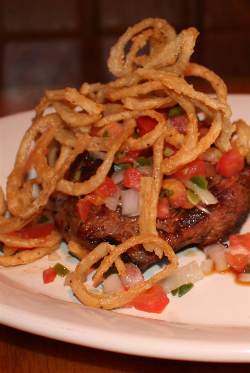 grilled steak with fried onions and tomatoes