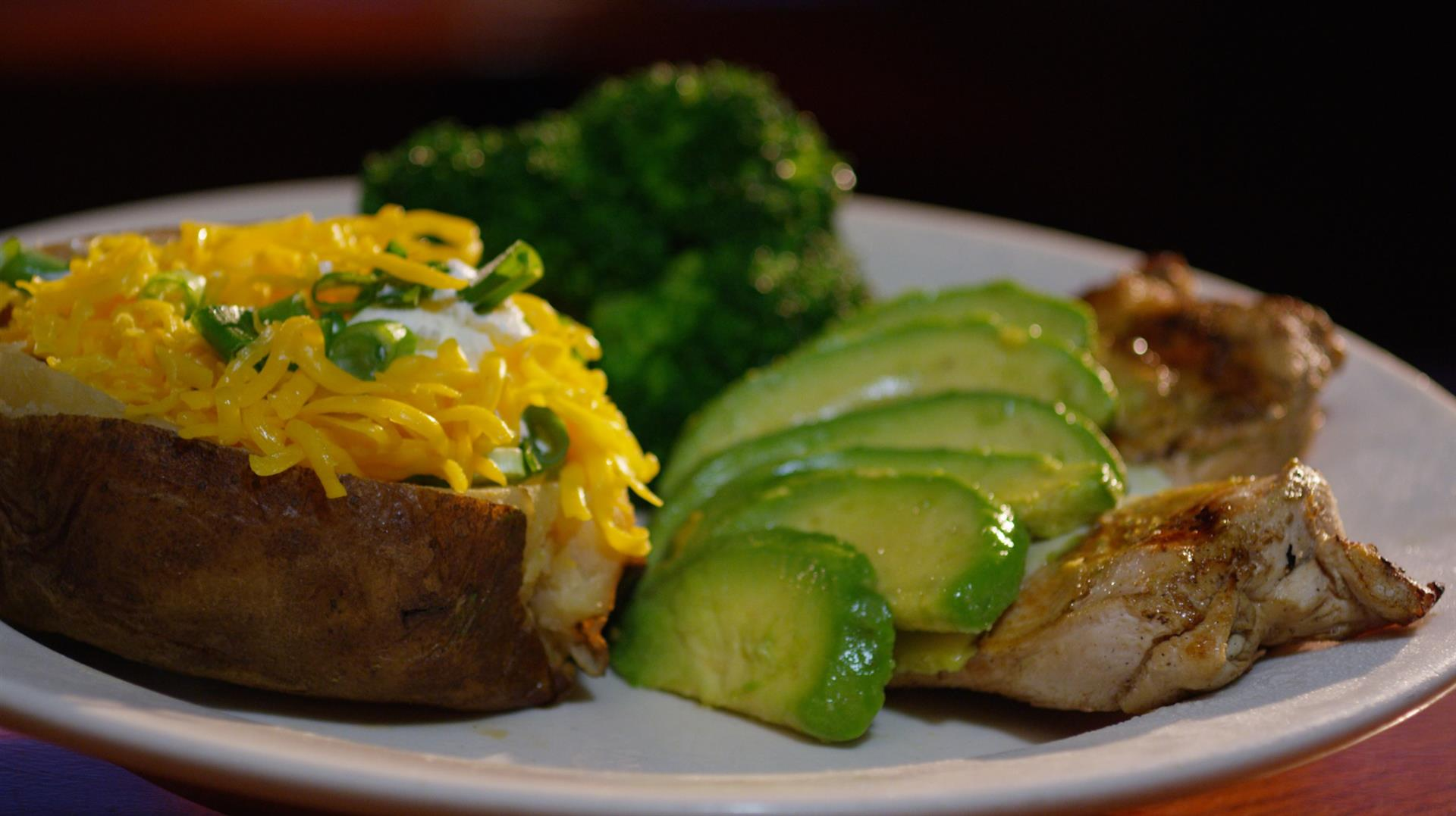 chicken with avocado and a baked potato with a side of broccoli